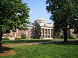 grass lawn with large brick building with columns and dome in background
