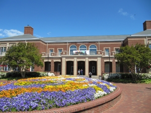 Large red brick building with brick pathway with flowers