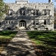Grey stone building with grass lawn in front at Kenyon College