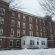 Large red brick colonial building in the snow