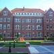 Large collegiate red brick building with white trim