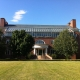 Large red brick building with grass lawn in front