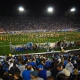 Collegiate band performing on football field at night