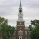 Large colonial red brick building with clock tower and steeple